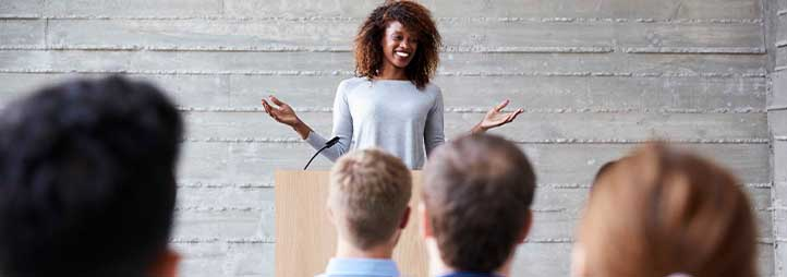 woman standing at a podium in front of crowd