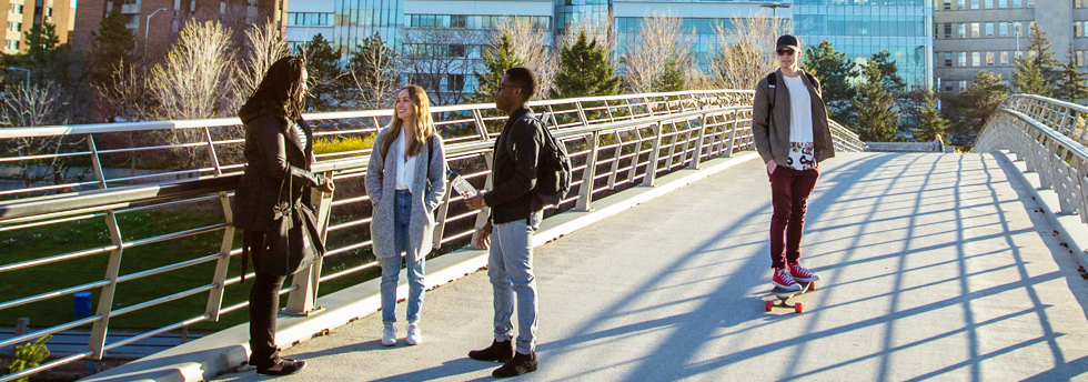 trois étudiants debout et un sur une planche à roulettes sur le pont piétonnier