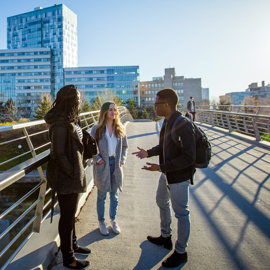 three students standing on pedestrian bridge in front of the Social Sciences building