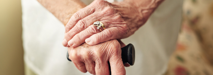 elderly woman's hands holding a cane